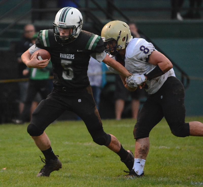 PMG PHOTO: DAVID BALL - Estacada QB Isaiah Schaffer pulls away from Astorias T.J. Colvin to finish off a 15-yard touchdown run that put the first points on the scoreboard.