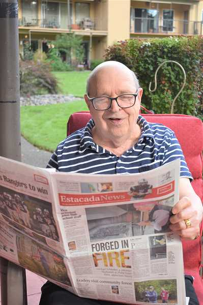 PMG PHOTO: EMILY LINDSTRAND - Former newspaper owner and publisher Bill James reads through a recent issue of the Estacada News.