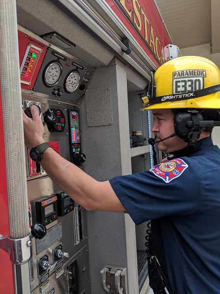 PMG PHOTO: EMILY LINDSTRAND - Estacada firefighter Nick Wettlaufer uses one of the fire districts new communication headsets. The Estacada Fire Volunteer Association is fundraising to purchase more headsets.
