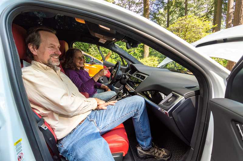 PMG PHOTO: CLARA HOWELL  - Mark Callicotte and Christy Clark check out the electric vehicles at Lake Oswego's EV Fair Sept. 21.