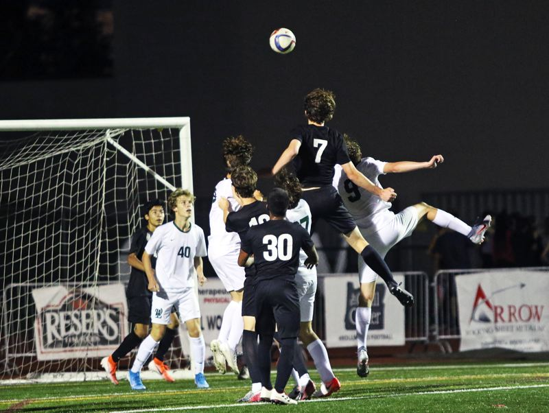 PMG PHOTO: DAN BROOD - Tualatin High School senior Hunter Popma (7) goes up high to score on a header shot, coming off a corner kick, during the Timberwolves' 3-2 win over West Linn.