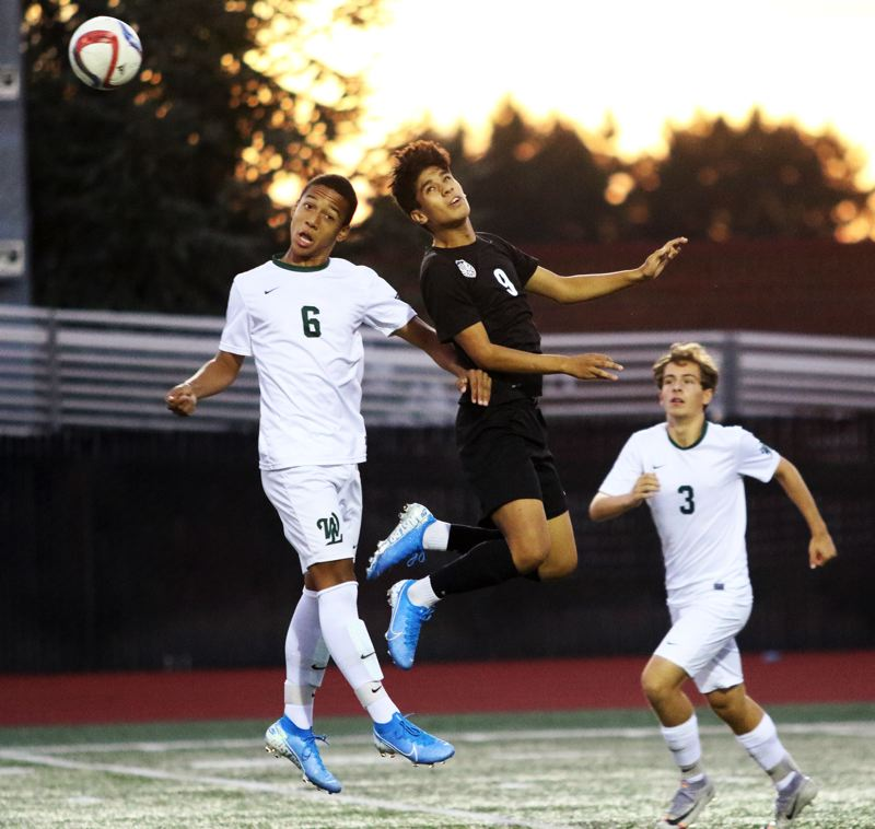 PMG PHOTO: DAN BROOD - West Linn sophomore Alejandro Valdes (6) and Tualatin junior Emmanuel Mayares go up for the ball during Tuesday's Three Rivers League contest.