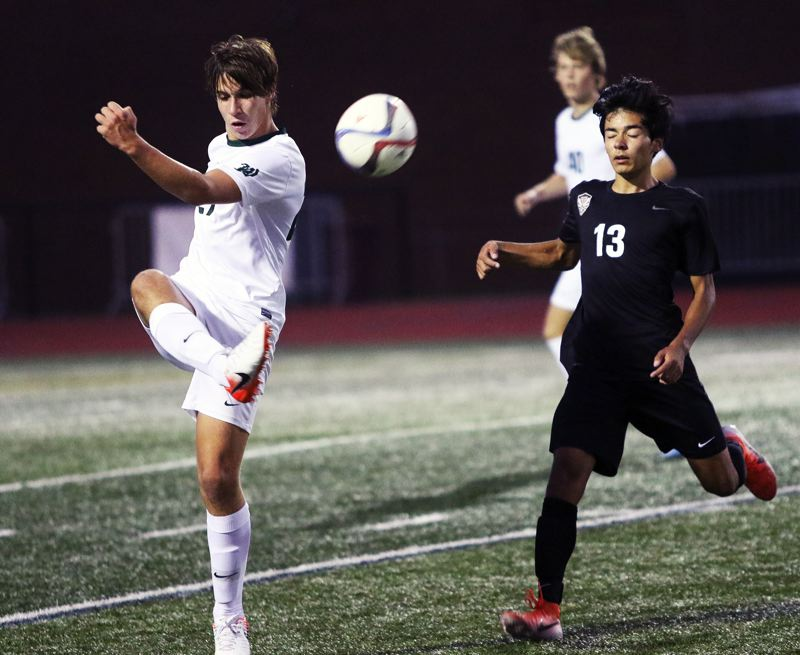 PMG PHOTO: DAN BROOD - West Linn senior Jacob Babalai (left) boots the ball past Tualatin freshman Remus Repcak during the Wolves' 3-2 win in Tuesday's Three Rivers League match.