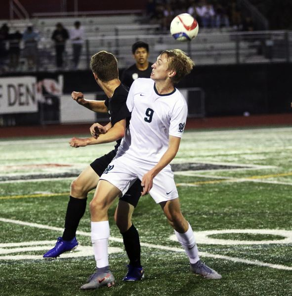 PMG PHOTO: DAN BROOD - West Linn High School senior Kyle Gregg (9) battles for the ball during the Lions' Three Rivers League match at Tualatin.