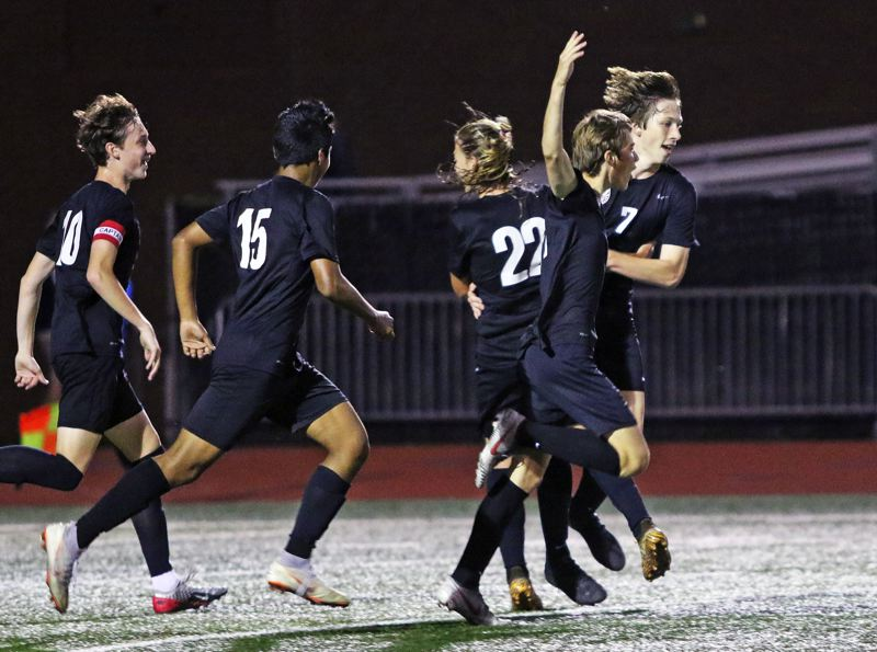 PMG PHOTO: DAN BROOD - Members of the Tualatin High School boys soccer team celebrate following a goal by senior Hunter Popma, which gave the Wolves a 3-0 lead over West Linn at the time.