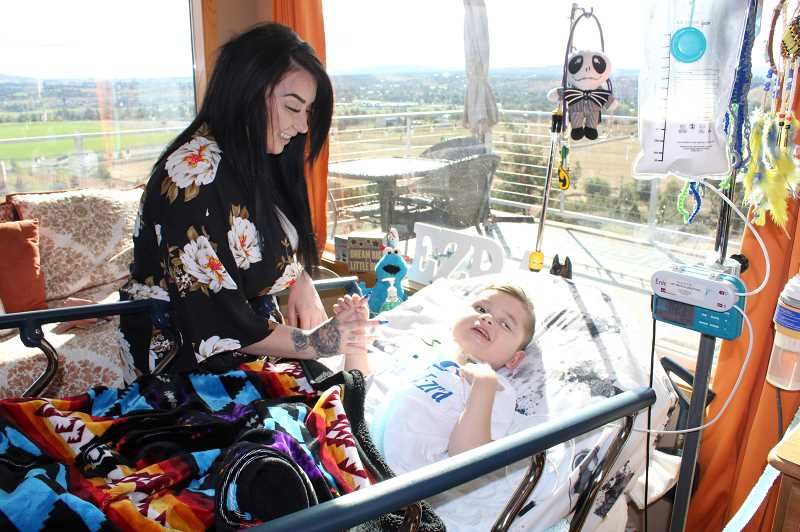 HOLLY M. GILL/MADRAS PIONEER - Despite suffering from a respiratory infection, Ezra Thomas, 4, has a smile for his mother, Kaytlynne Rogerson, from his hospital bed in the middle of the living room of his grandparents, Tina and Eric Jorgensen, on Friday. Ezra, who suffered a traumatic brain injury in November 2017, is now legally blind, and relies on tubes for breathing and feeding. Just hours later, he was airlifted to Doernbecher Children's Hospital, where he remained on Wednesday.