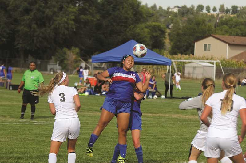 STEELE HAUGEN/MADRAS PIONEER - Jiana Smith-Francis heads in a goal during the Lady Buffs' 3-1 victory Sept. 19.