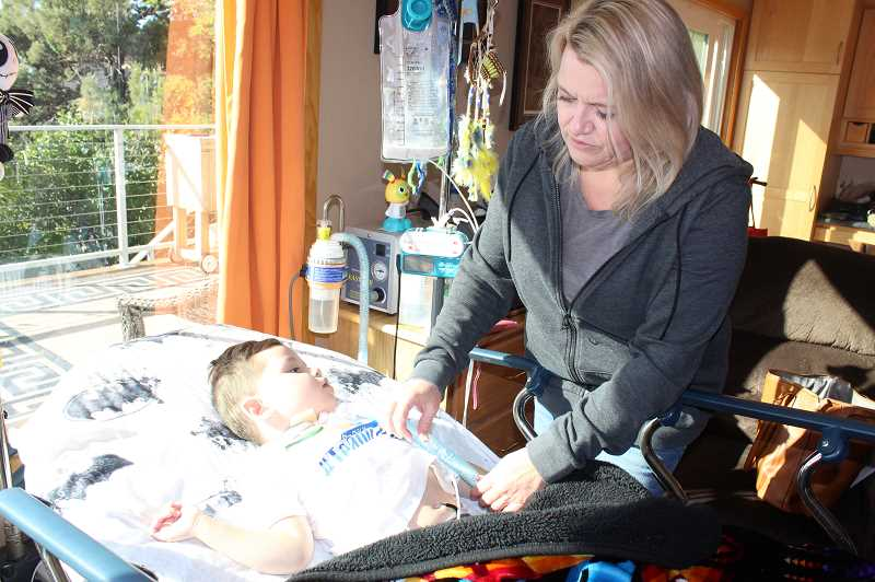 HOLLY M. GILL/MADRAS PIONEER - Tina Jorgensen checks her grandson's feeding tube on Friday, when he was suffering from respiratory problems. On Wednesday, Ezra was in intensive care at Doernbecher Children's Hospital, in Portland.
