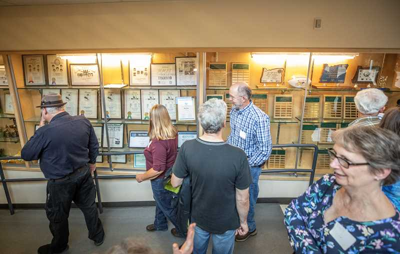 TIDINGS PHOTO: JONATHAN HOUSE - Classmates from the West Linn Class of 74 check out the schools athletic awards during a Friday tour.  6. Sue Bradley, left, talks about West Linns auditorium during a tour for members of the Class of 74.