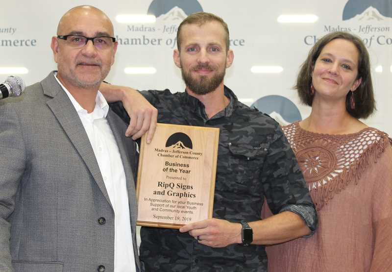 HOLLY M. GILL/MADRAS PIONEER - Brandon Searcy and his wife, Amber, who own and operate RipQ Signs and Graphics, accept the Business of the Year award from J.R. Brooks.