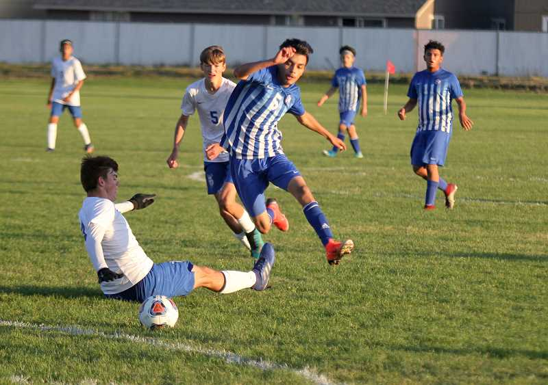 STEELE HAUGEN - Geraldo Penaloza jumps over a Mazama defender, who is trying to make a slide tackle.