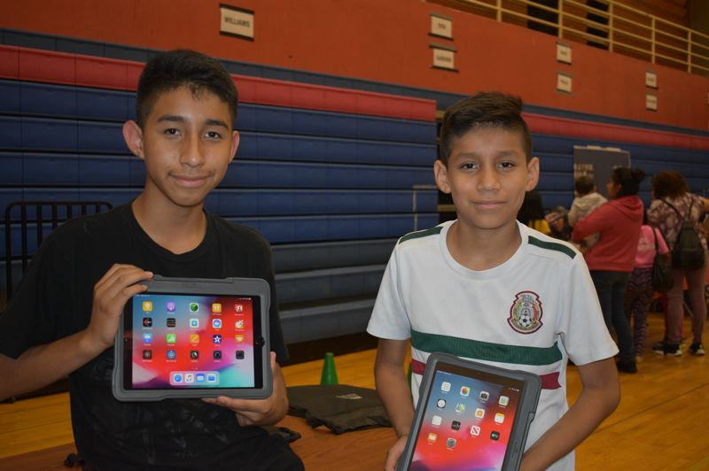 PMG PHOTO: TERESA CARSON - Basilio Angel Grano, an eighth grader at Reynolds Middle School and his sixth grade brother Santiago show off their new iPads. Every middle school student in the Reynolds School District got the computers to take home courtesy of Verizon.