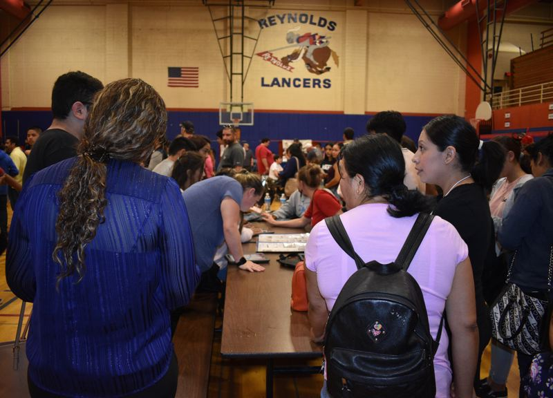 PMG PHOTO: TERESA CARSON - After receiving their new tablets Wednesday, Sept. 25, the Lancers headed to tables set up in the gym, where teachers helped the students activate their computers.