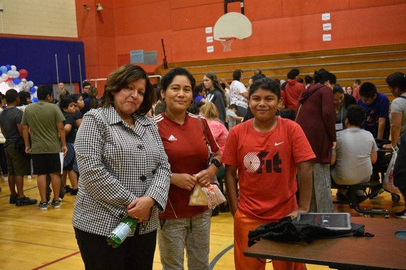 PMG PHOTO: TERESA CARSON - Reynolds School District Superintendent Danna Diaz chats with Reyna Reyes and her seventh grader Jareth, who was thrilled to get his own computer.