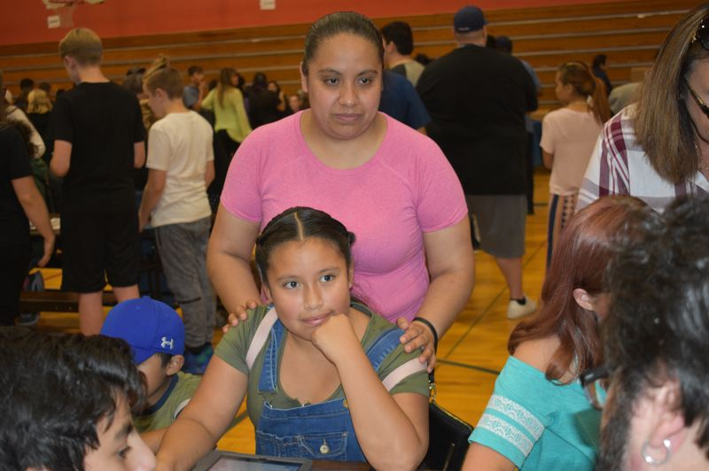 PMG PHOTO: TERESA CARSON - Sixth-grader Alondra Suarez waited with her mom to get her computer up and running. Suarez considers math her favorite subject and said the computer is 'going to help to do homework. It's exciting.'
