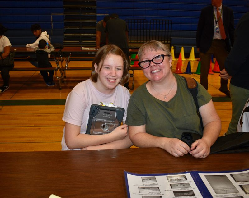 PMG PHOTO: TERESA CARSON - Sophie Crowder, a seventh grader, sits with her mom, Nikke, after getting her computer. She explained that teachers want assignments turned in via computer these days.