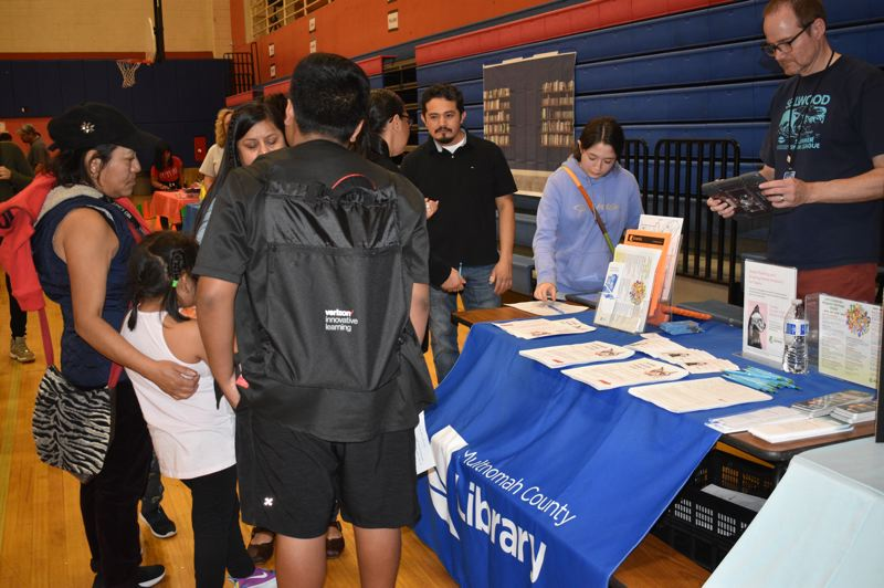 PMG PHOTO: TERESA CARSON - The Multnomah County Library was on hand at the Reynolds Middle School iPad hand outs to let students now about all the many online services the library offers. Folks can stream movies, download e-books and more.