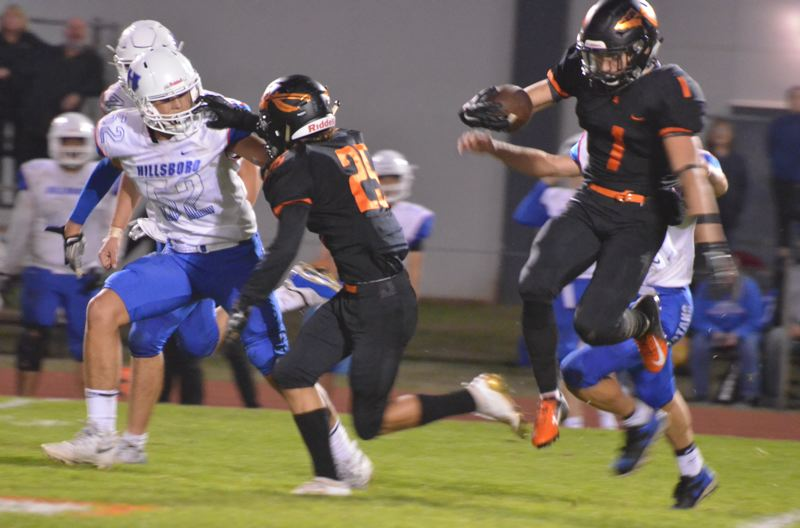COURTESY PHOTO: JOHN BREWINGTON - Blake Morkert (right) makes a runback for Scappoose as Colton Frates blocks during the Indians'  47-30 victory over Hillsboro last week.