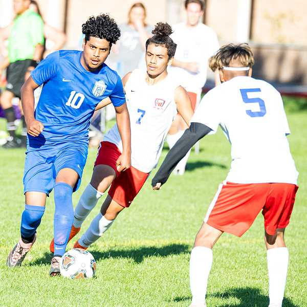 LON AUSTIN/CENTRAL OREGONIAN - Elias Villagomez pushes the ball up the field against a pair of Lebanon defenders. Villagomez and the Cowboys lost 6-0 to the Warriors. Crook County will host Hood River Valley on Tuesday beginning at 4:30 p.m.