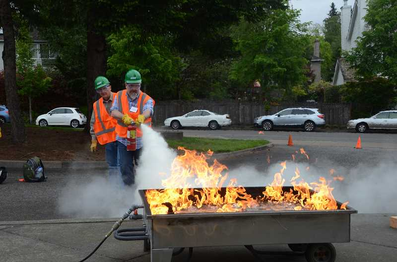 COURTESY PHOTO - Past class participants use a portable fire extinguisher to put out a small fire.