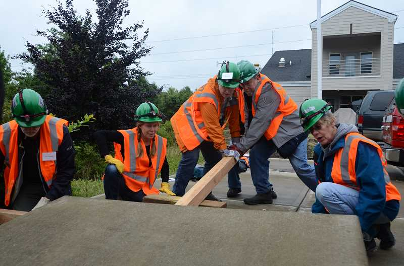 COURTESY PHOTO - Past CERT trainees use a piece of wood as a fulcrum to lift a concrete slab, simulating a situation where they would help someone who had an object fall on them.