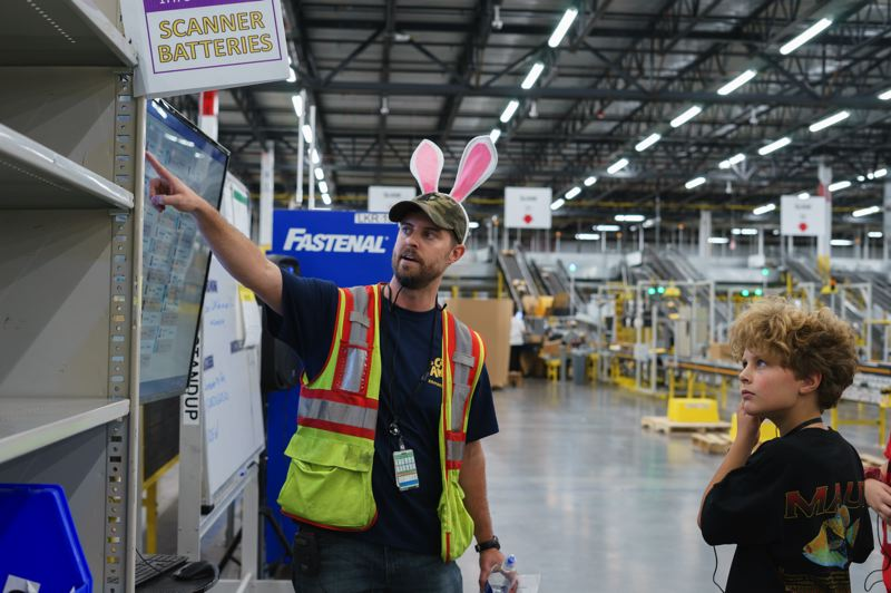 COURTESY PHOTO: AMAZON FULFILLMENT CENTER  - An Amazon Fullfillment Center employee shows a young visitor how the sorting system works in the vast Troutdale facility on Thursday, Sept. 26.