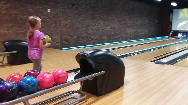 PMG PHOTO: RAY PITZ - Leah MacCluer bowls in one of 22 alleys on the bottom floor of the Langers entertainment center Friday, the first day the building was open to the public.