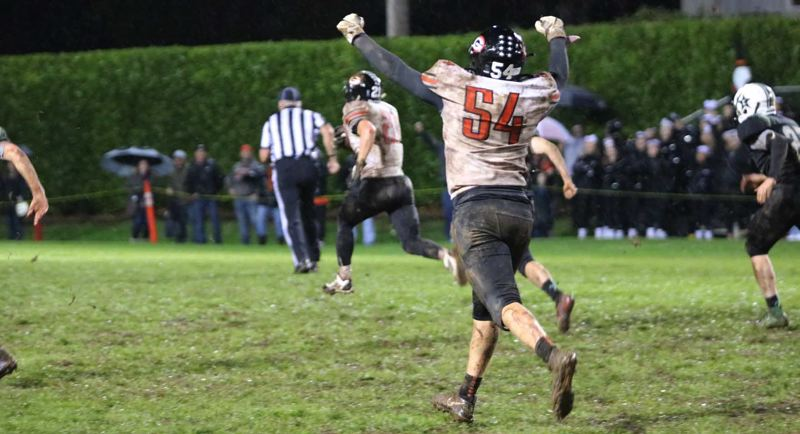 PMG PHOTO: JIM BESEDA - Gladstone's Brady Fox (54) reacts as senior tailback Mason Scheehean (21) breaks loose on a 65-yard touchdown run with 5:19 to play, helping to seal the Gladiators 23-20 win over Estacada.