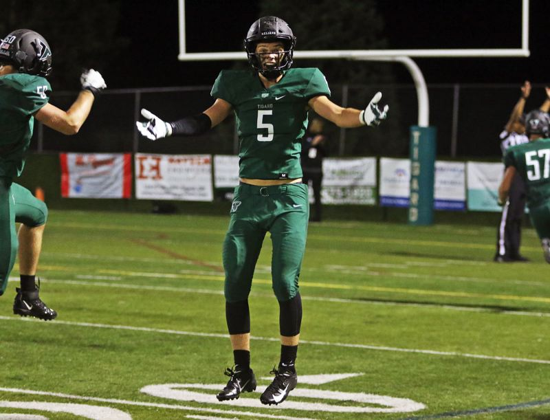 PMG PHOTO: DAN BROOD - Tigard High School senior Andrew Carter (5) celebrates following a 54-yard touchdown run by Tiger senior Hunter Gilbert during Tigard's 31-7 win over Lake Oswego.