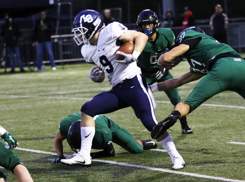 PMG PHOTO: DAN BROOD - Lake Oswego senior Casey Filkins (9) looks for running room during the Lakers' Three Rivers League game at Tigard on Friday.