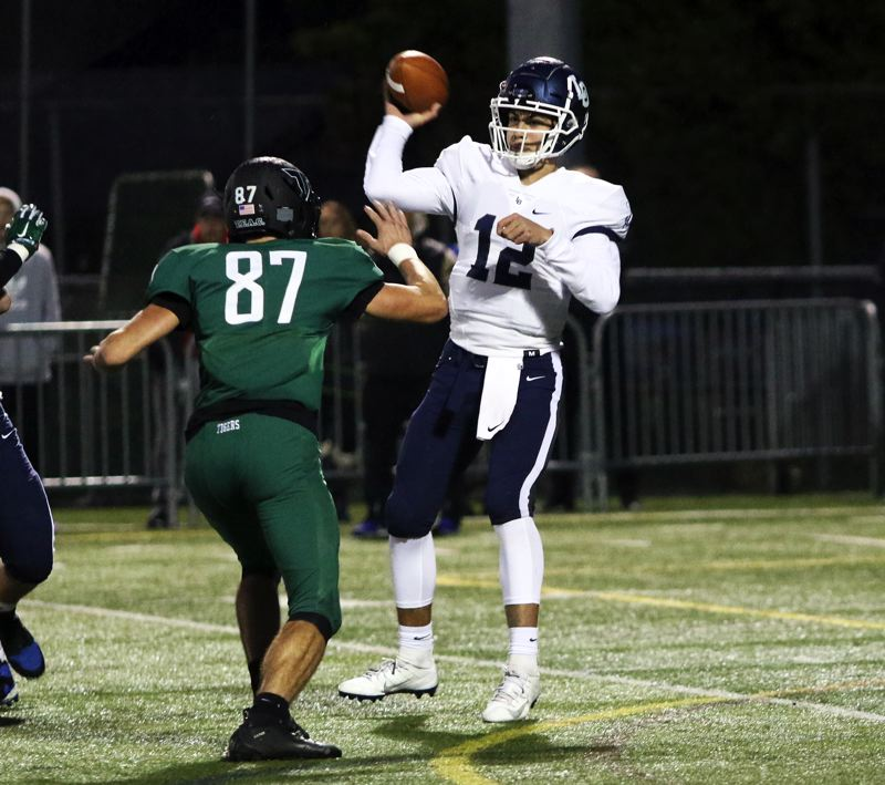 PMG PHOTO: DAN BROOD - Lake Oswego junior quarterback JJ Woodin (right) looks to throw over Tigard senior Kamryn Hosley during Friday's Three Rivers League showdown.