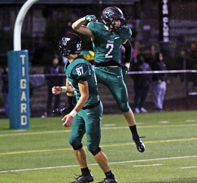 PMG PHOTO: DAN BROOD - Tigard High School seniors Tyler Penn (2) and Kamryn Hosley celebrate following Penn's 48-yard touchdown pass reception in the Tigers' 31-7 win over Lake Oswego.