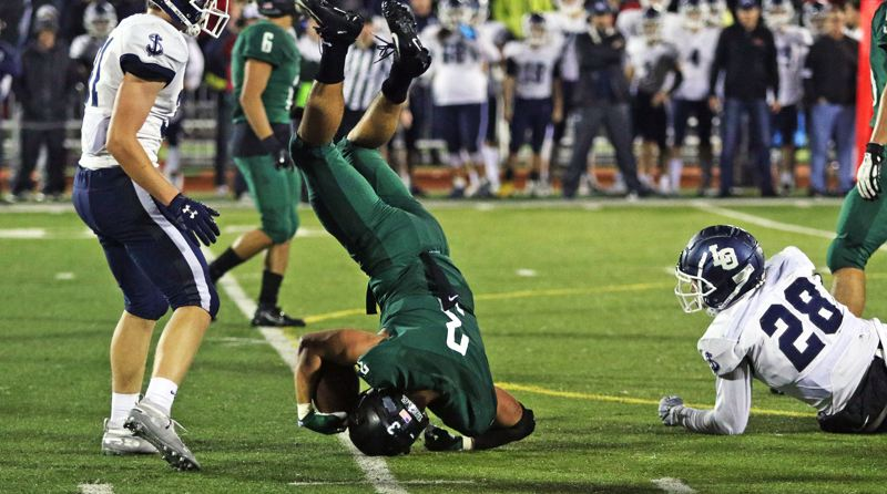 PMG PHOTO: DAN BROOD - Tigard High School senior running back Hunter Gilbert gets turned upside down by Lake Oswego's Aaron Olson (left) and Zach Mahan during Friday's game.