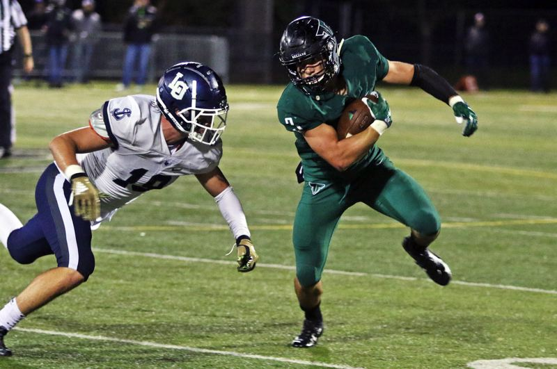PMG PHOTO: DAN BROOD - Tigard High School senior running back Hunter Gilbert (right) looks to get past Lake Oswego senior Marshall McGuire during Friday's game.