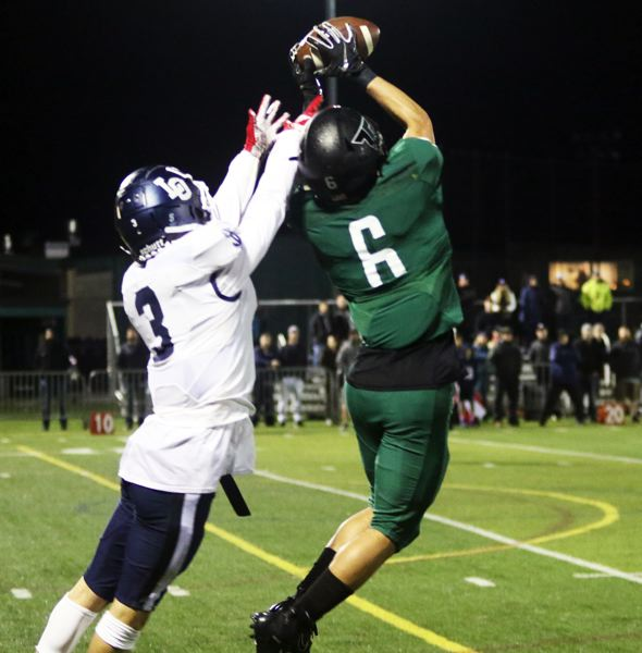 PMG PHOTO: DAN BROOD - Tigard High School senior Max Lenzy (right) makes a leaping reception against Lake Oswego senior Joe Hutson during Friday's game.