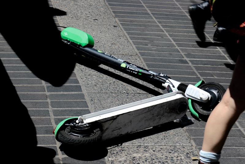 PMG PHOTO: ZANE SPARLING - Members of a crowd walked past a fallen Lime electric scooter in Portland recently.