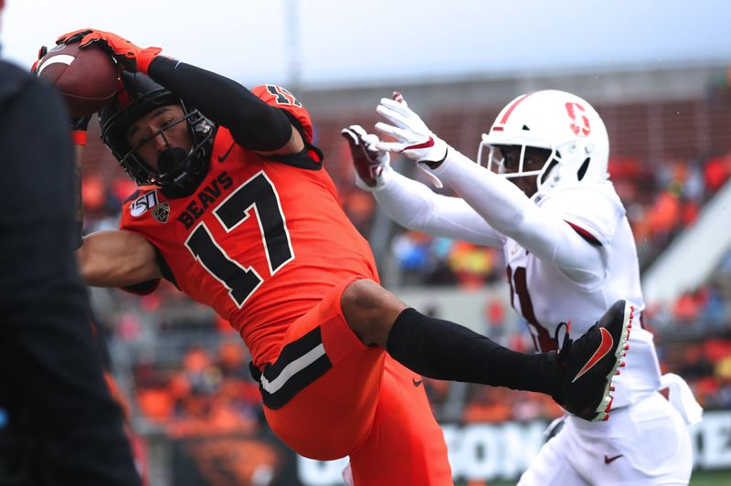 PMG PHOTO: JAIME VALDEZ - Oregon tate Beavers wide receiver Isaiah Hodgins (left) makes a reception over Stanford Cardinal cornerback Paulson Adebo (11) in the first half at Reser Stadium.
