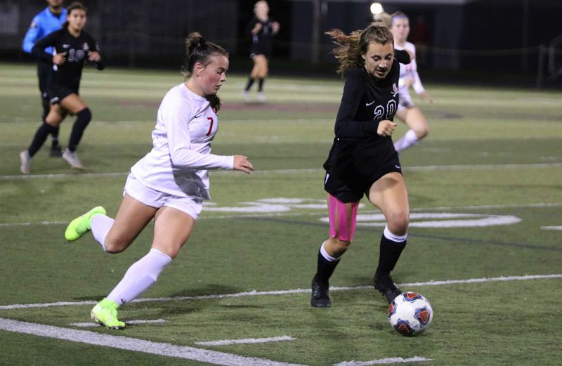 PMG PHOTO: JIM BESEDA - Oregon City forward Bree McCullough (7) tries to use her speed to get past Clackamas defender Paizlee Whalen (20) during the second half of Thursday's non-conference girls soccer game.