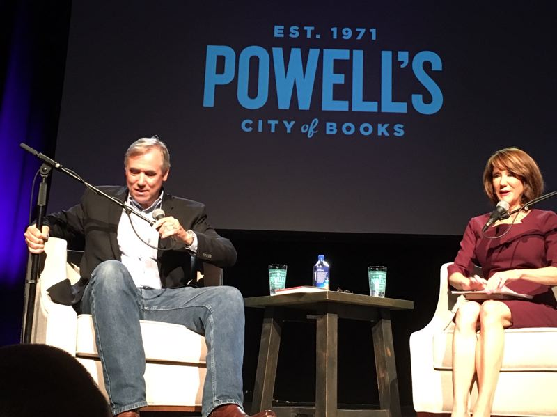 PMG PHOTO BY PETER WONG - U.S. Sen. Jeff Merkley, D-Ore., adjusts his microphone during an appearance Aug. 26 at Revolution Hall in Portland sponsored by Powell's Books. At right is Laural Porter, anchor for Portland television station KGW who asked questions of Merkley.