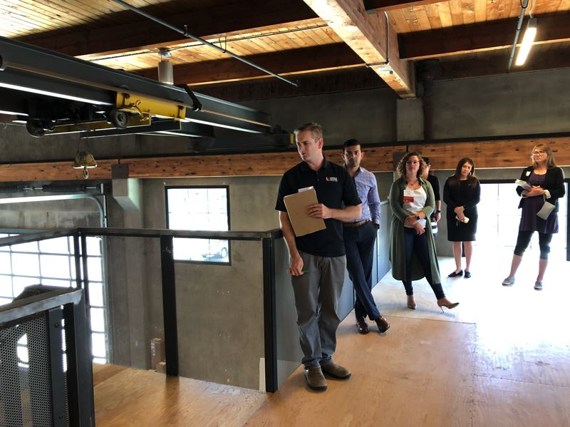 PMG PHOTO: STEPHANIE BASALYGA - Erik Frame, left, a project manager with Lorentz Bruun Construction, points out details of the building during a tour of The Glass Lab organized by CREW Portland.