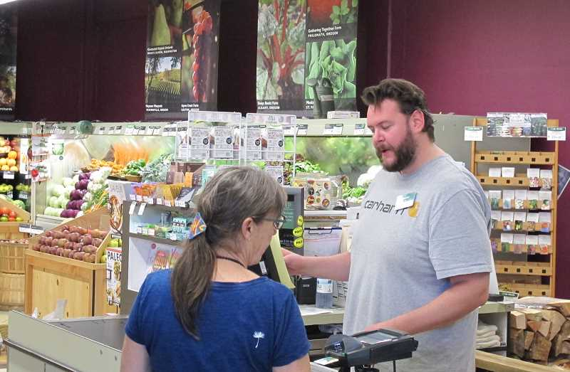 PMG PHOTOS: BILL GALLAGHER -  Food Front cashier Sam Lynch, like most of the employees, is a member of the United Food and Commercial Workers union Local 555.