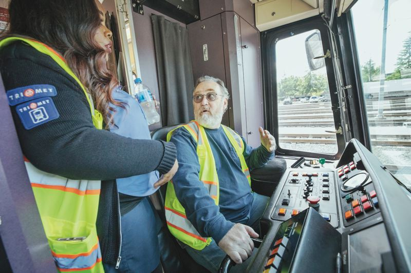PMG PHOTO: JONATHAN HOUSE - Portland Tribune reporter Jim Redden gets instructions from TriMet train conductor Brittany Hall on operating a MAX train at the Elmonica Rail Operating Facility.