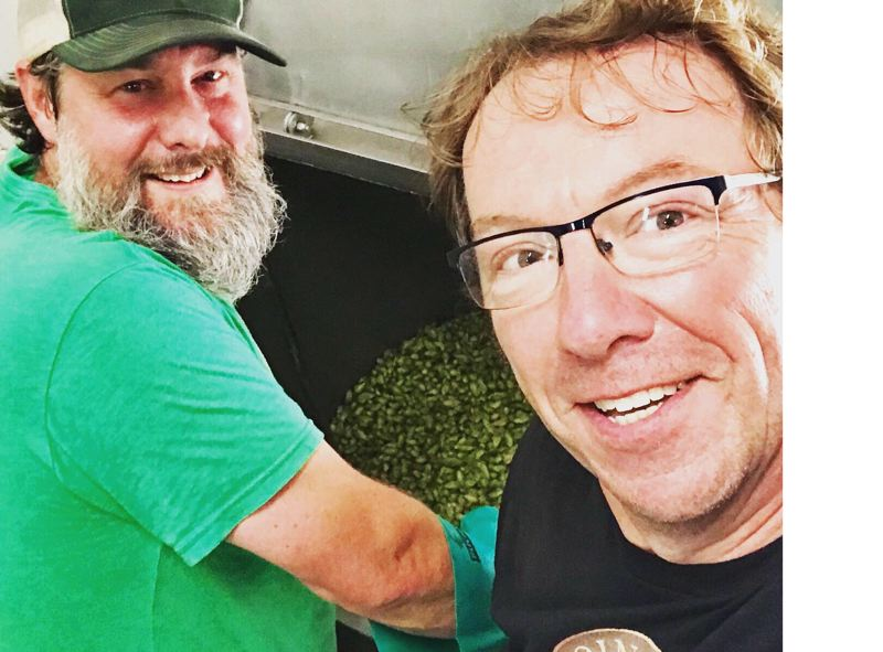 COURTESY PHOTO - Chip Conlon, new head brewer, pulls in a batch of fresh hops with Tim Hohl, founder of Coin Toss Brewing in Oregon City.