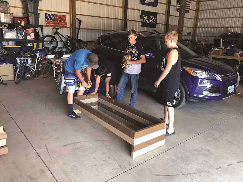 COURTESY PHOTO - From left, Williamson, Shawn Ostrander, Jameson Guido and Joshua Williamson spent two weeks assembling, sanding, and painting the flower boxes for French Prairie Nursing and Rehab.