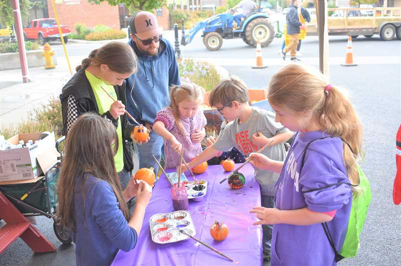PMG PHOTO: EMILY LINDSTRAND - Community members paint pumpkins during the Estacada Harvest Festival on Saturday, Sept. 28.