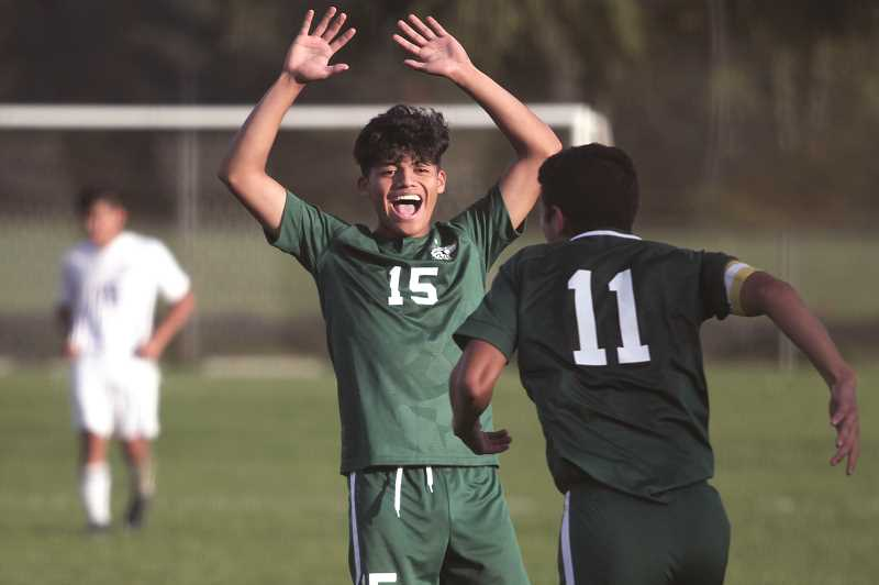 PMG PHOTO: PHIL HAWKINS - Forward Isaac Santiago celebrates fellow senior Barsilay Carrillos second goal of the game in the final minutes against Madras on Sept. 25. Carrillo scored both goals to give the Huskies a 2-0 win, their first of the season.