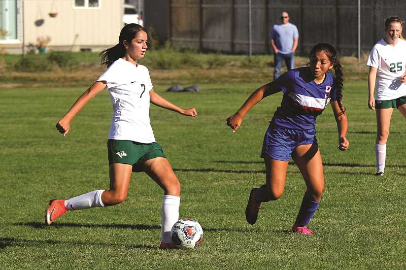 PMG PHOTO: STEELE HAUGEN - North Marion's Katie Zapata advances the ball up the field in the Huskies' 4-1 win over Madras.