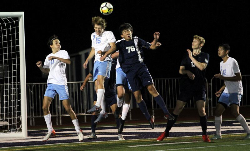 PMG PHOTO: MILES VANCE - Lakeridge's Sam Hardie (No. 15) goes up for a header against Lake Oswego's Christian Waarvick during the Lakers' 4-3 win at Lake Oswego High School on Thursday, Sept. 26.