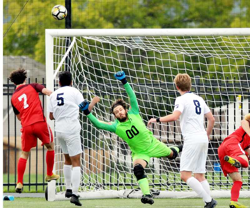 GRAPHIC PHOTO: GARY ALLEN - George Fox University goalkeeper Cole Benton, a junior, puts his body on the line to stop a shot in GFU's game against Linfield on Saturday in Newberg. The Bruins lost 2-1 in double overtime after scoring the first goal of the contest.
