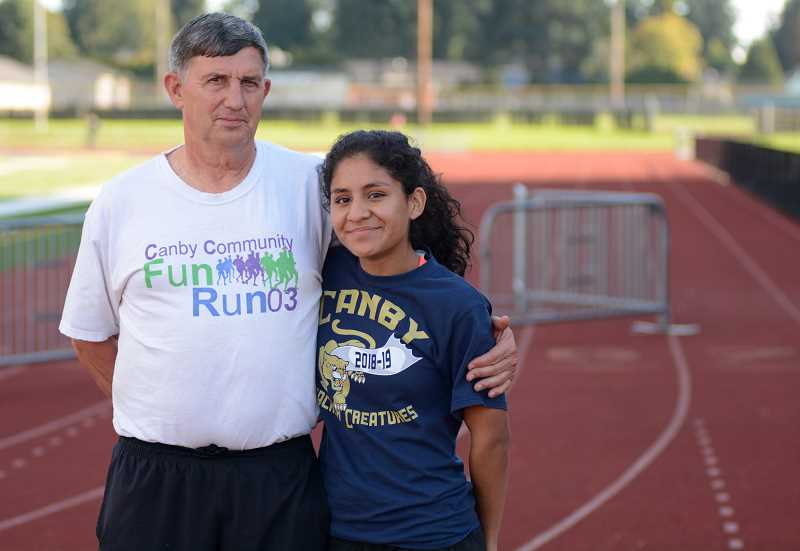 PMG PHOTO: DEREK WILEY - Canby senior Jennifer Torres, with cross country coach Tom Millbrooke, has already PR'd by neraly a minute and 20 seconds this season.